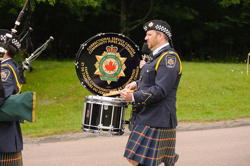 A photo of one member of CSC's pipes and drums playing a drum while marching in a parade.