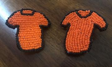 Deux petits chandails perlés transformés en épinglettes que le personnel peut porter en souvenir de l'importance de la vérité et de la réconciliation.
